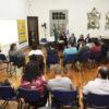 Pessoas em reunião, em semicírculo, com pessoas sentadas em fileira à parte acompanhando a reunião