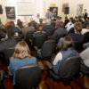Auditório com pessoas sentadas, assistindo a um palestrante em pé