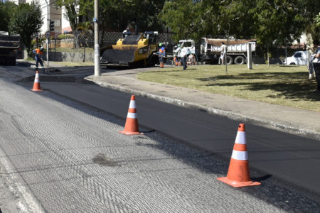 Rua com asfalto novo e cones de sinalização