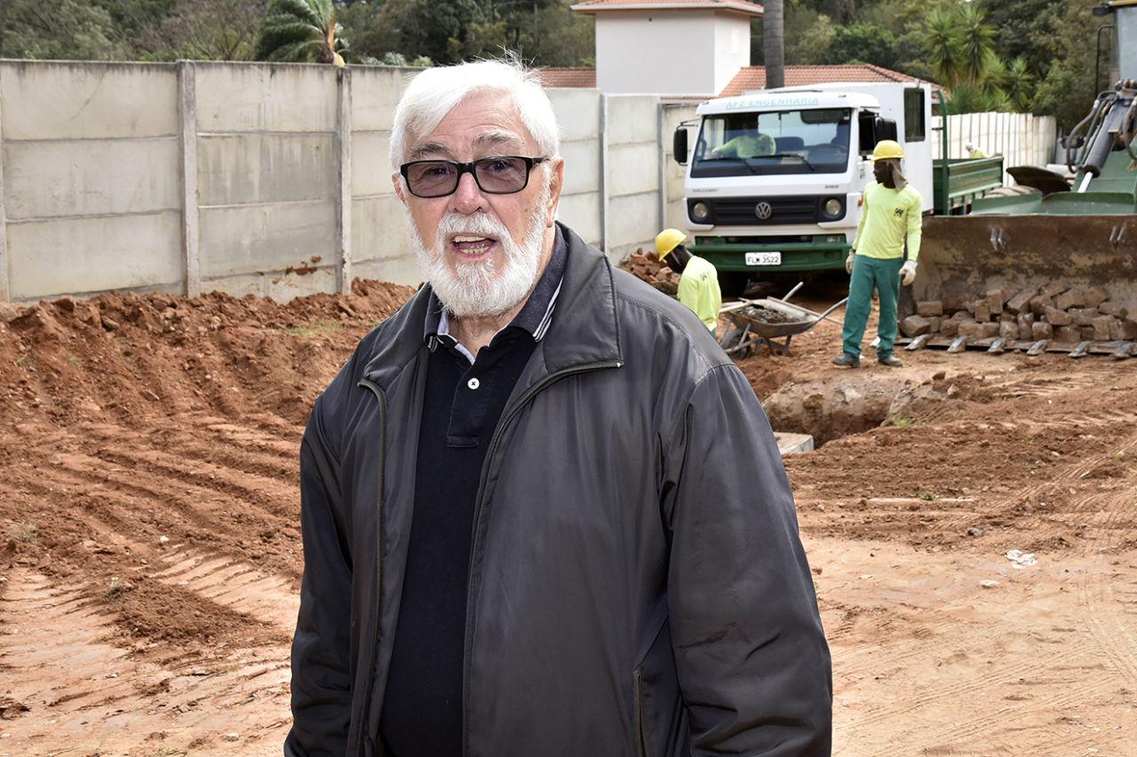 Homem em pé com caminhão e trabalhadores atrás