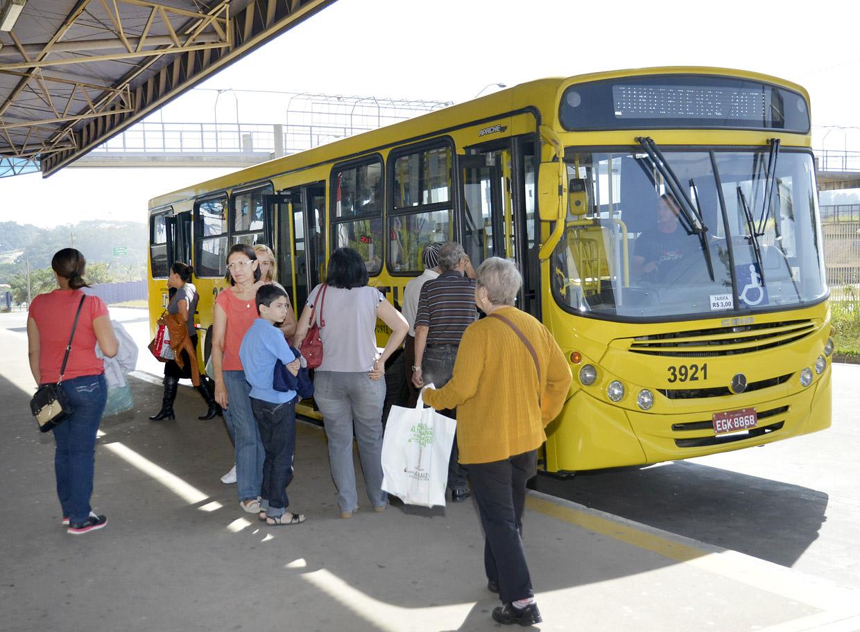 Passageiros em fila sobem em ônibus estacionado