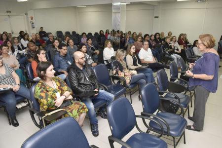 Mulher fala para plateia sentada