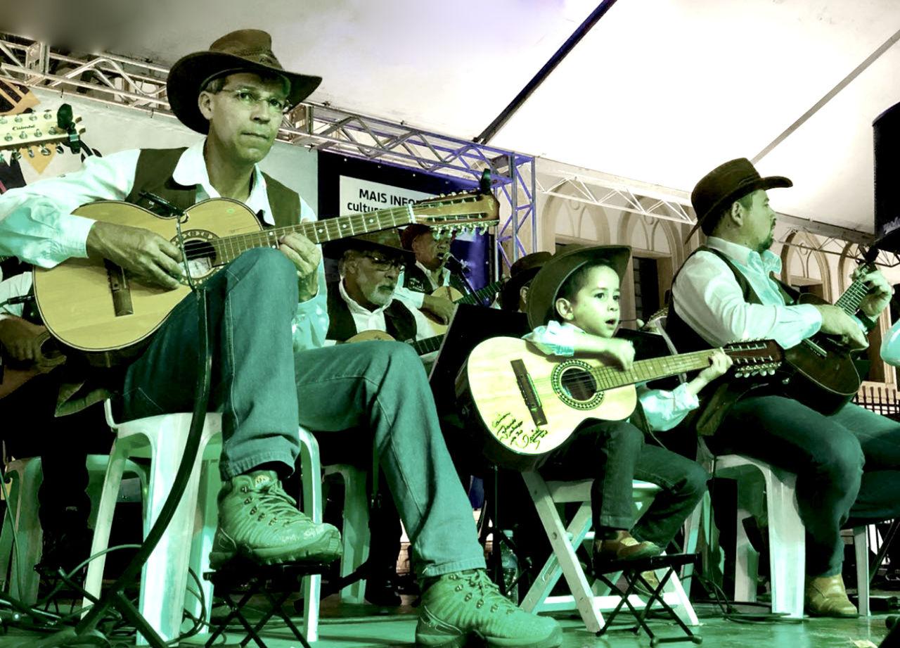 Dois homens adultos e uma criança sobre palco, tocando violão