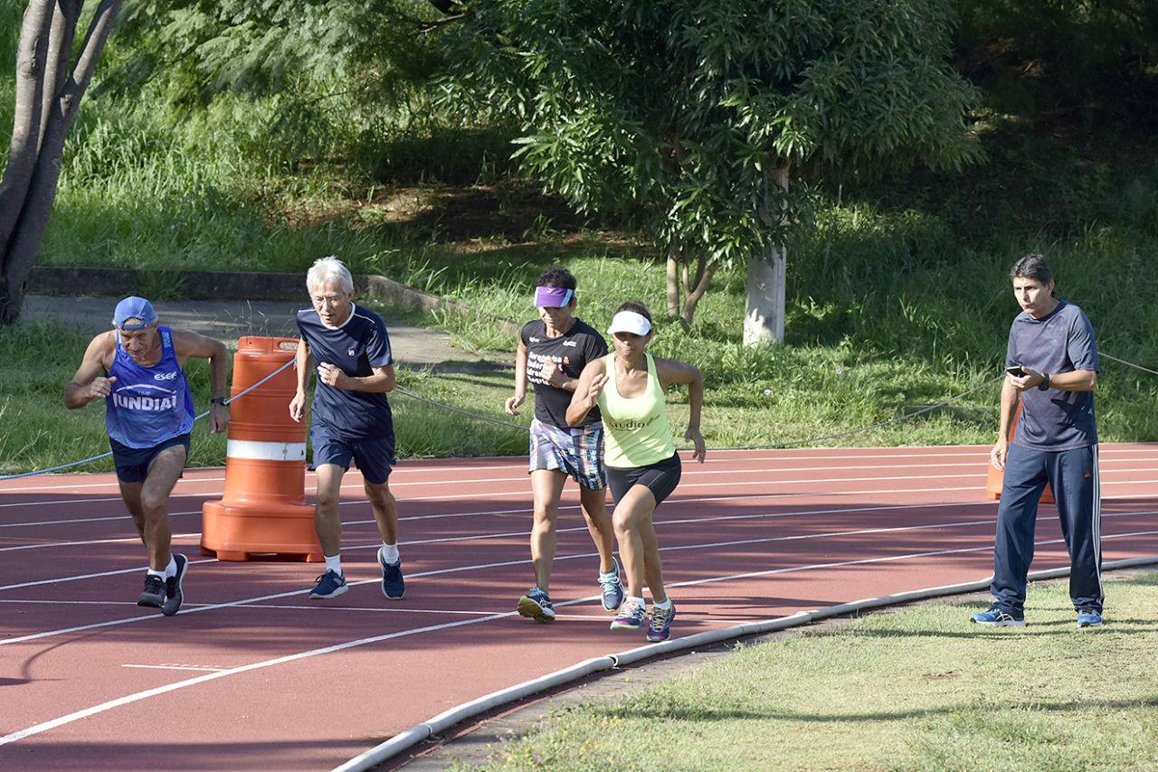 Quatro pessoas correm na pista de atletismo enquanto outra segura cronômetro