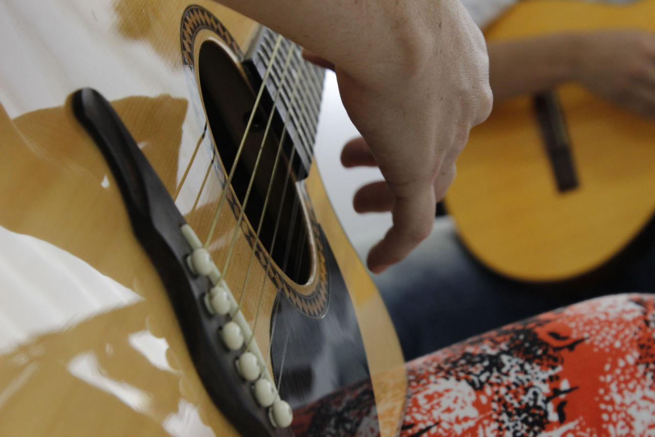 Mão tocando violão e ao fundo outro violão sendo tocado