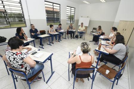 Grupo de adultos sentado em cadeiras, dispostas em formato circular, conversando