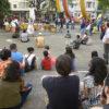 Pessoas sentadas no chão em uma praça, em torno de um palco improvisado