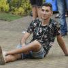 Rapaz sentado no chão, com pernas cruzadas e braço apoiado no chão, com rosto de quem está se divertindo enquanto assiste