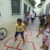 Crianças em um corredor, algumas em fila, enquanto aguardam um menino pulando amarelinha, com bicicleta apoiada em muro