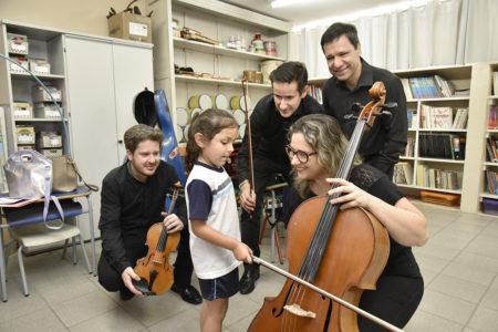 Criança uniformizada segura o arco de um violoncelo, com a atenção de músicos