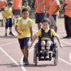 Em primeiro plano, criança correndo ao lado de uma criança portadora de deficiência física. Ao fundo voluntários observando o desenvolvimento da atividade
