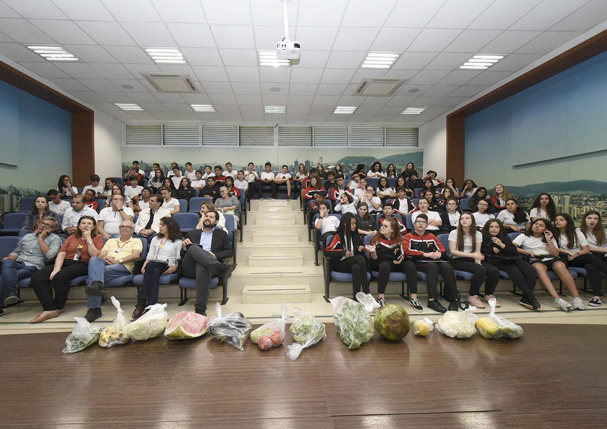 Auditório em vários níveis com pessoas sentadas, com olhares voltados em direção à câmera, com alimentos em sacolas dispostos sobre mesa