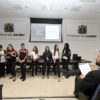 Jovens em pé, em frente a auditório, com detalhe do prefeito sentado, de costas, assistindo à apresentação