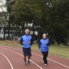 Um homem e uma mulher uniformizados correndo em pista de atletismo, com ginásio ao fundo