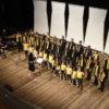 Foto do alto com crianças e jovens cantando, perfilados sobre palco