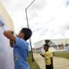 Meninos pintando parede com rolo de tinta
