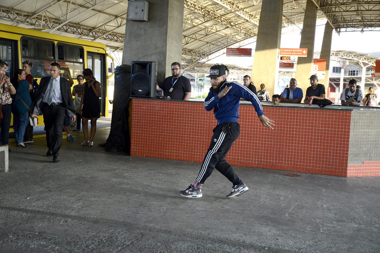Dançarino em performance em plataforma de terminal de ônibus