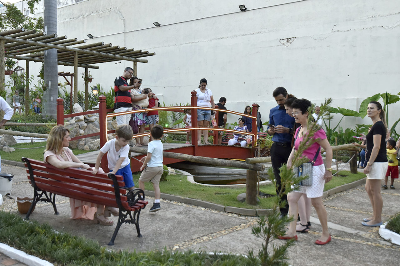 Jardim com ponte sobre tanque de água, com adultos e crianças