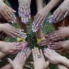Mãos femininas com unhas esmaltadas em cores diversas