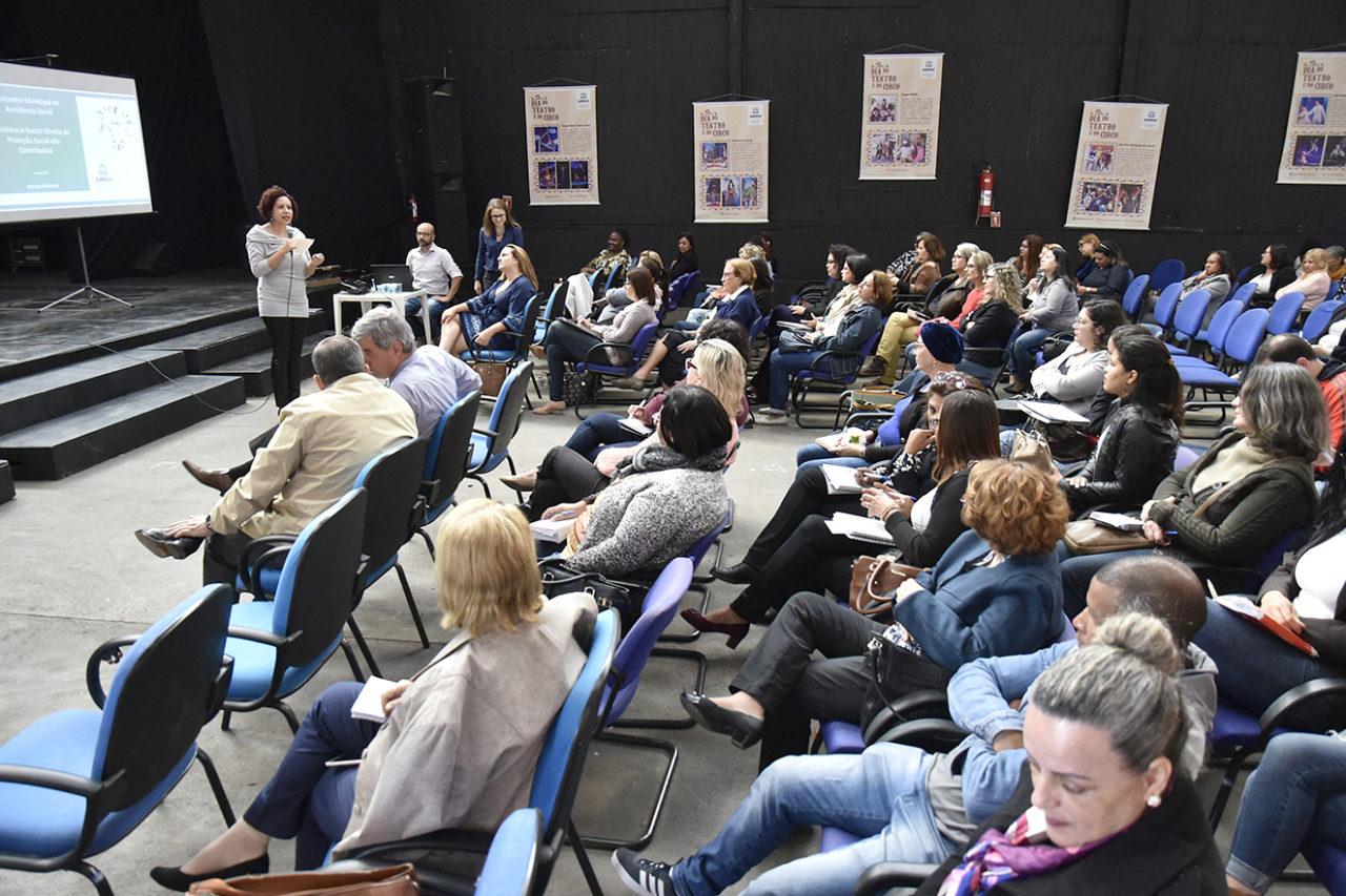 Foto de auditório com cadeiras ocupadas e palestrantes à frente