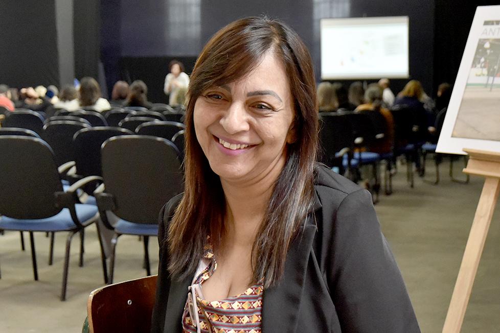 Mulher em foto espontânea, com auditório ao fundo