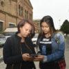 Duas mulheres conversam e manuseiam um celular, com prédio de tijolos à vista ao fundo