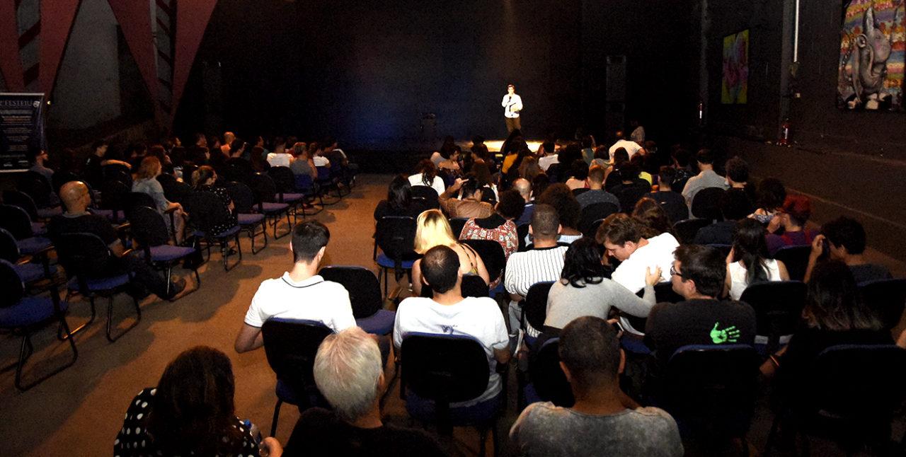 Auditório com pessoas sentadas e palestrante no palco