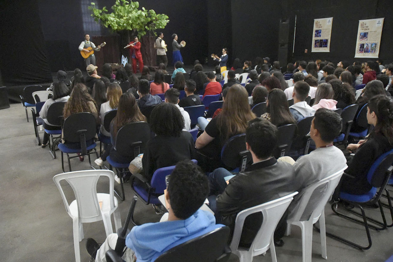 Sala de espetáculos com pessoas sentadas, assitindo a espetáculo no placo