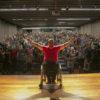 Foto posada de homem sentado em cadeira de rodas, com os braços abertos, e plateia ao fundo