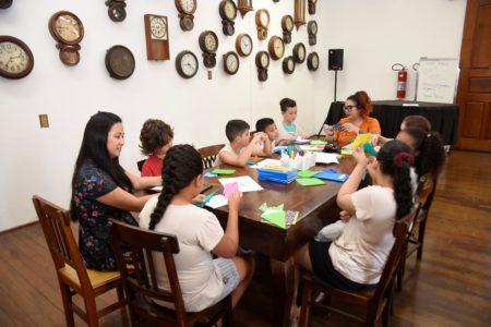 crianças sentadas em volta de uma mesa, fazendo dobraduras de papel