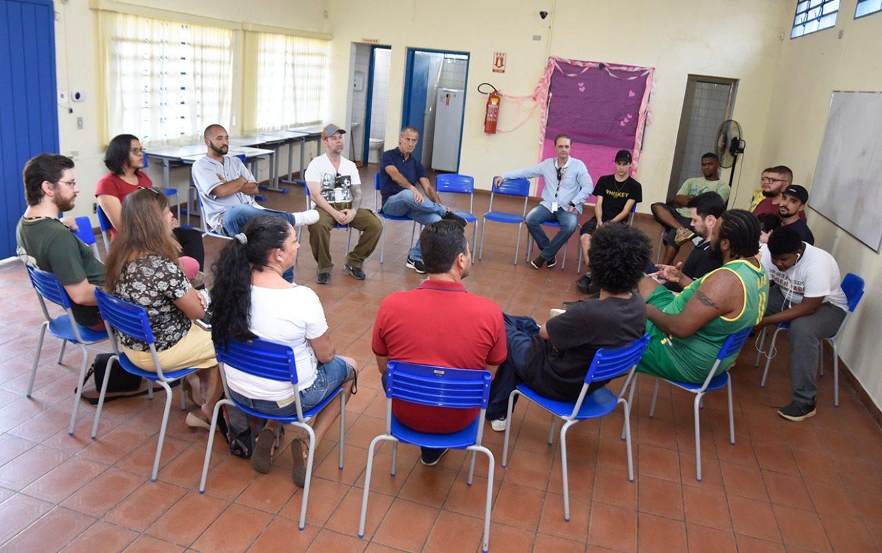 Pessoas sentadas em uma grande roda numa sala