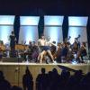 Palco do teatro,com músicos tocando e bailarinos em performance