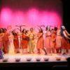 11 mulheres sobre palco com recipientes de vidro com terra e fumaça sobre o palco