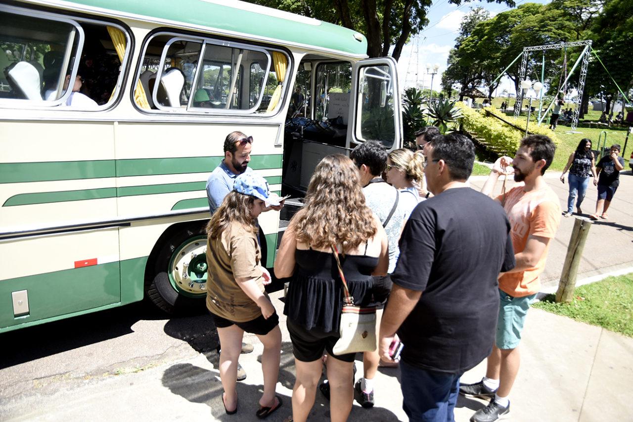 Pessoas em fila, aguardando para embarcar em ônibus estacionado na rua