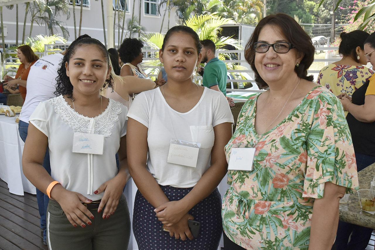 Três mulheres uma ao lado da outra em foto posada, com crachás pendurados sobre o peito