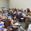 Sala de aula com pessoas sentadas e palestrante em pé à frente