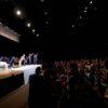 Foto lateral de teatro, com bailarinos no palco para cumprimentos e plateia aplaudindo