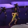 Bailarinos em performance sobre palco, com dois travesseiros gigantes