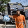 Coletor de lixo se aproxima de lixeira e toca em saco, com caminhão ao fundo