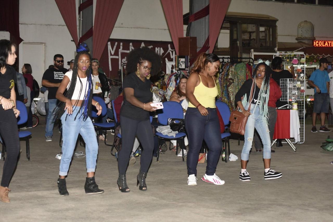 Meninas arriscam passos de dança, uma ao lado da outra