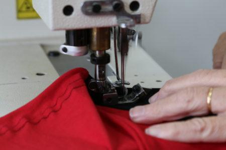 Aluno costurando com ajuda de máquina profissional
