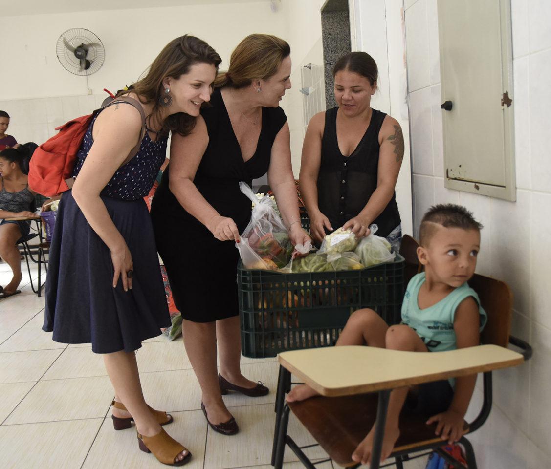 Três mulheres em pé checam verduras e legumes dentro de uma caixa, com um garoto sentado em uma cadeira em frente