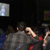 Pessoas sentadas em sala escura, asssistindo a filme sendo projetado em telão branco