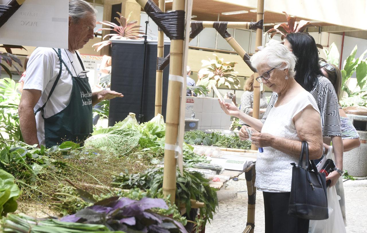 Mulher em frente à banca de verduras