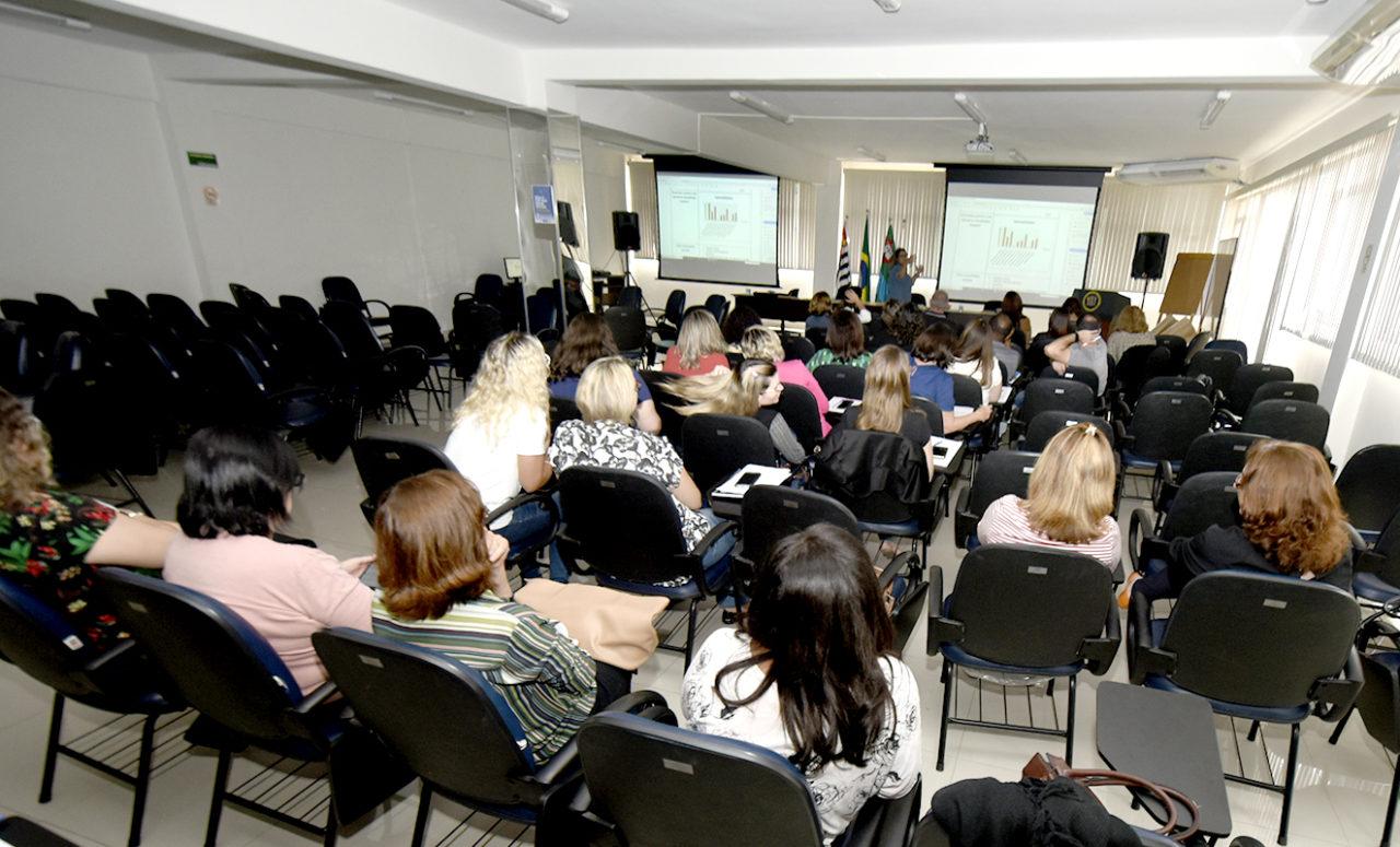 Auditório com pessoas sentadas com palestrante à frente