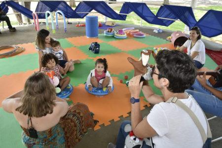 Crianças pequenas em atividade lúdica sobre piso emborrachado, seguindo instruções de monitores