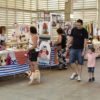 Adultos com criança e com cachorro pequeno em coleira caminhando entre barracas de artesanato