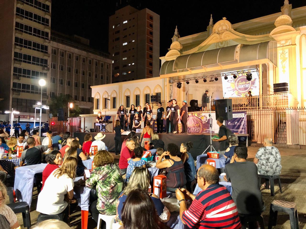 Plateia acompanha apresentação de coral em cima de palco