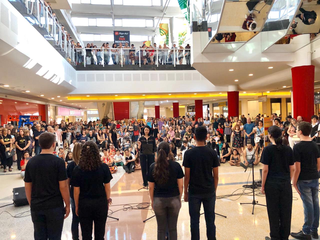 Foto de costas de coralistas cantando, com público espalhado pelo shopping assistindo