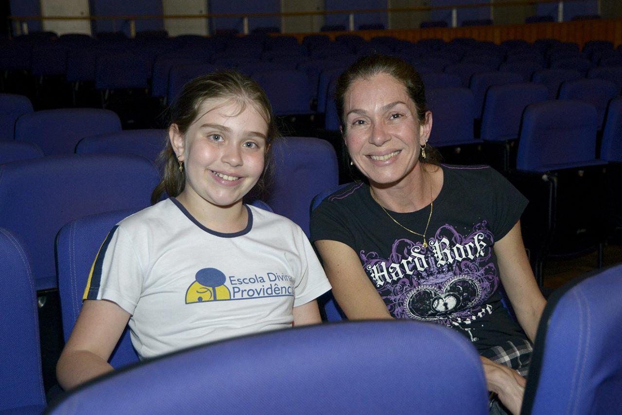 Foto posada de menina ao lado a mãe, sentadas em plateia de teatro